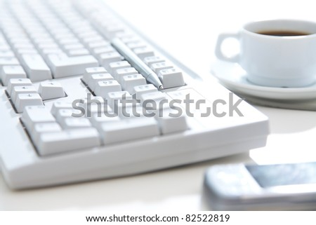 Close-up of white keyboard, cellphone, pen and a cup of coffee on the desktop - stock photo
