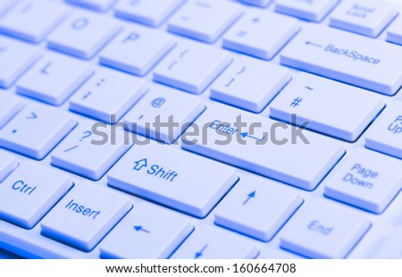 Close up of white keyboard  with blue lighting effect for concepts of digital technology electronic media and the internet - stock photo
