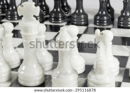 Close-up of white king on chess game opening. Marble board