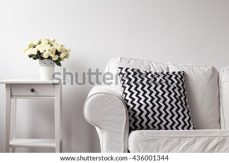 Close up of white night table and white sofa with pattern pillow on couch - stock photo