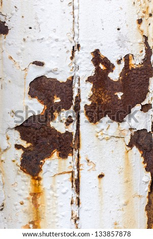 Close up of white paint pealing off of metal with rust stains - stock photo