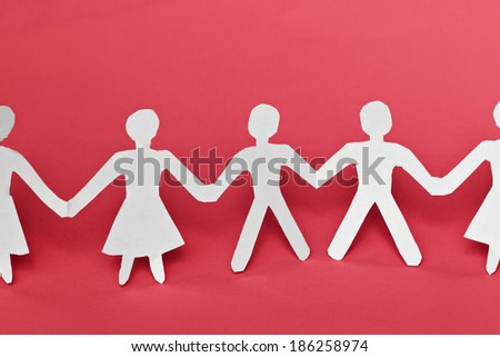 Close up of white paper people on red pink background - stock photo