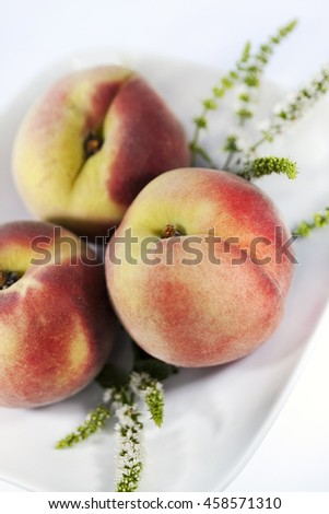 Close up of white peaches and herbs on a plate - stock photo