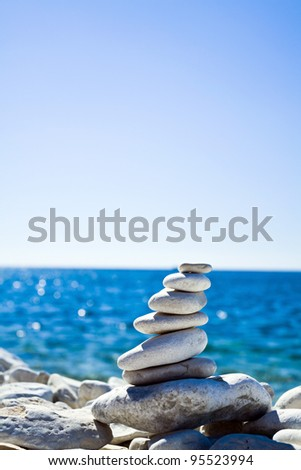 Close-up of white pebbles stack over blue sea - stock photo