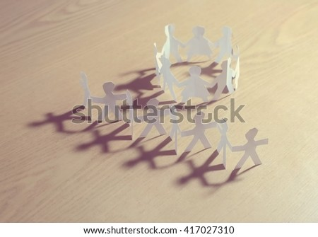 Close up of white people cut out of paper on wood (table) background. Peace, friendship, guard, protection, people unity concepts illustrated. - stock photo