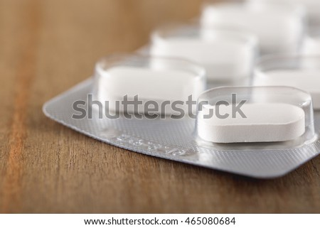 Close up of white pills in a plastic package on wooden background,Macro shot.