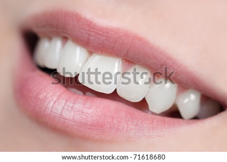 Close up of white, shiny and healthy smile. Intentional very shallow depth of field. - stock photo