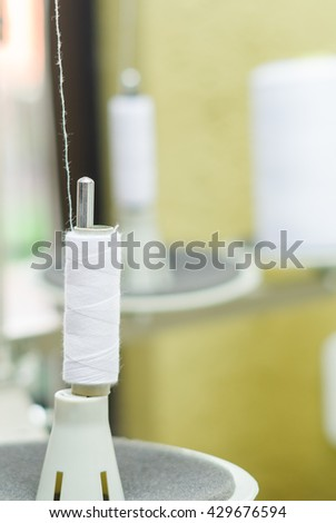 Close up of white spool of thread conected to a sewing machine