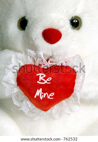 "Close-up of white teddy bear with ""Be Mine"" heart"