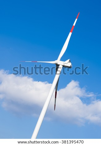 Close up of white wind turbine with generating electricity on blue sky. Alternative energy concept - stock photo
