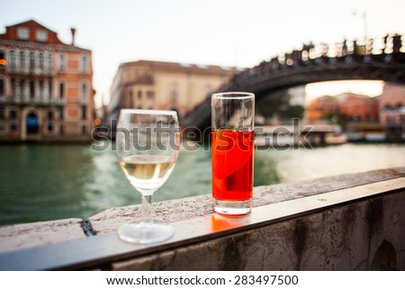 Close up of white wine glass and red cocktail with lemon - stock photo