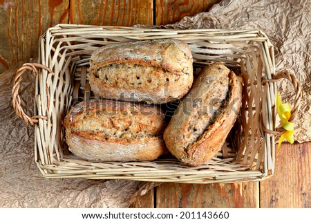 Close up of whole grain rolls placed in wooden bread basket