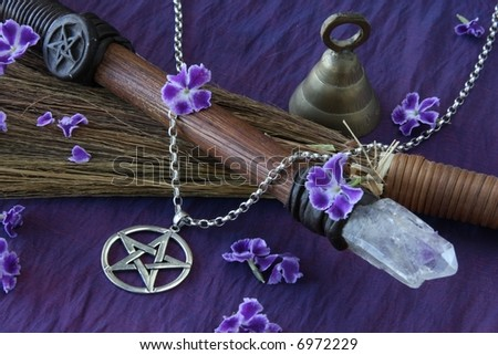 close up of wiccan objects - pentacle pendant wood / crystal wand bell and straw besom
