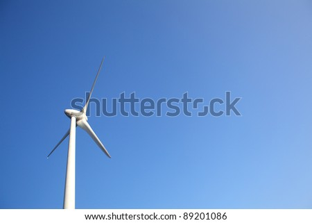 Close up of Windturbine producing alternative energy with a blue sky - stock photo