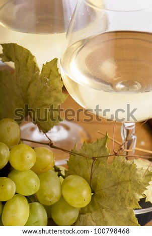 Close-up of wineglass with white wine with grape - stock photo