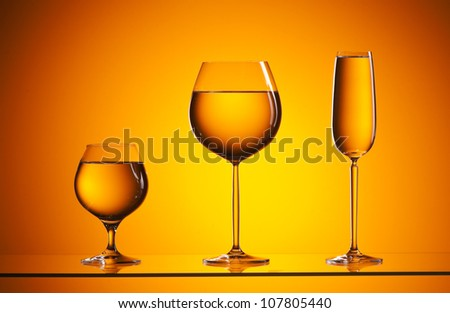 close-up of wineglasses with copyspace and abstract yellow background - stock photo