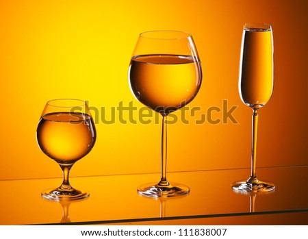 close-up of wineglasses with copyspace and abstract yellow background