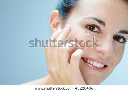 close up of woman applying eye cream - stock photo