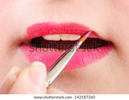 close up of woman applying lip gloss - stock photo