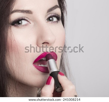 Close-up of woman applying lipstick. Model looks like Monica Bellucci.  Macro of nails, lips and lipstick - stock photo