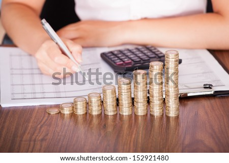 Close-up Of Woman At Work In Front Of Coin Graph - stock photo