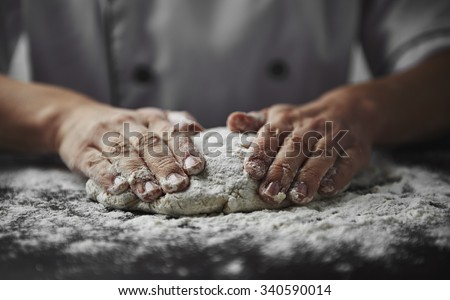 Close-up of woman baker hands kneading the dough on black board with flour powder. Concept of baking and patisserie.    - stock photo