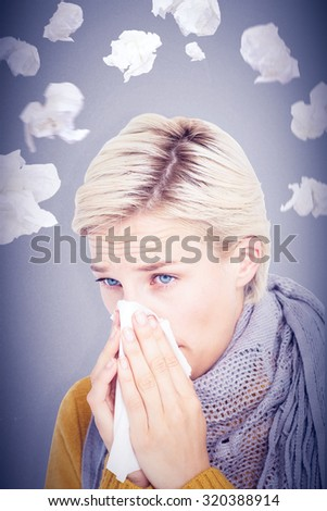 Close up of woman blowing her nose against grey background - stock photo