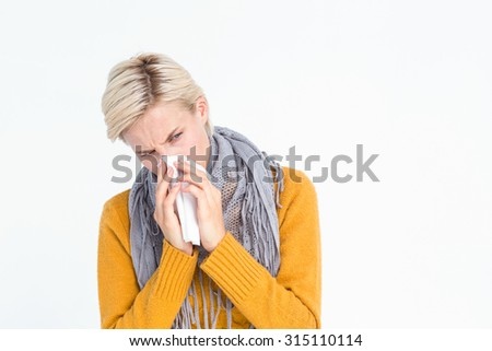 Close up of woman blowing her nose with a tissue - stock photo