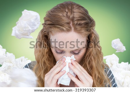 Close-up of woman blowing nose into tissue against green vignette