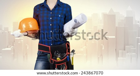 Close up of woman builder with hardhat and papers in hands - stock photo