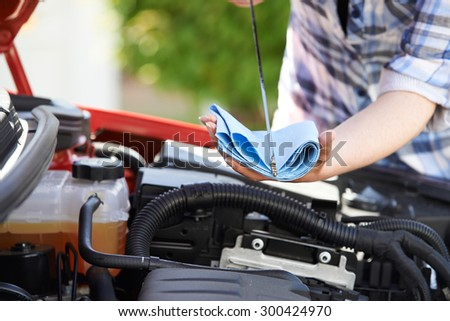 Close-Up Of Woman Checking Car Engine Oil Level On Dipstick - stock photo