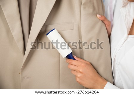 Close-up Of Woman Cleaning Coat With Adhesive Roller - stock photo