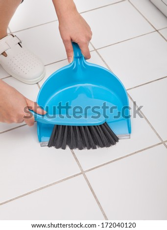 Close-up Of Woman Cleaning Floor With Broom And Dust Pan - stock photo