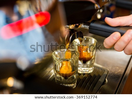 close up of woman doing espresso by coffee machine