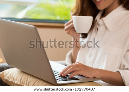 Close-up of woman drinking coffee while using laptop