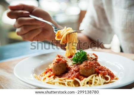 close up of woman eating spaghetti with fork  - stock photo