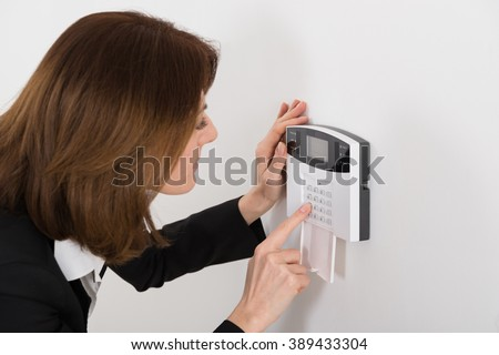 Close-up Of Woman Entering Code In Security System - stock photo