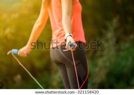 Close up of woman feet jumping, using skipping rope in park - stock photo