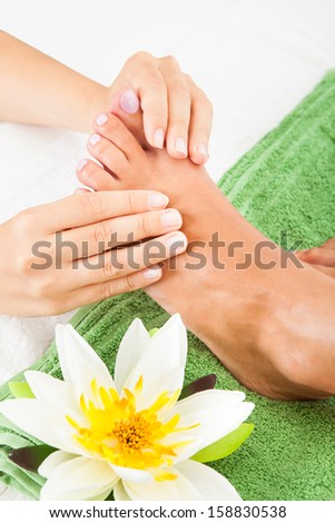 Close-up Of Woman Feet Receiving Foot Massage In Spa - stock photo