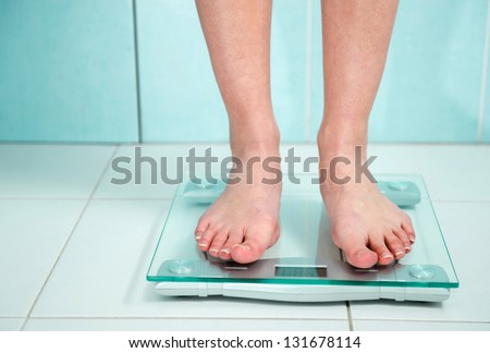 close-up of woman feet weighing in bathroom - stock photo
