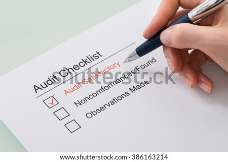 Close-up Of Woman Filling Audit Checklist Form - stock photo