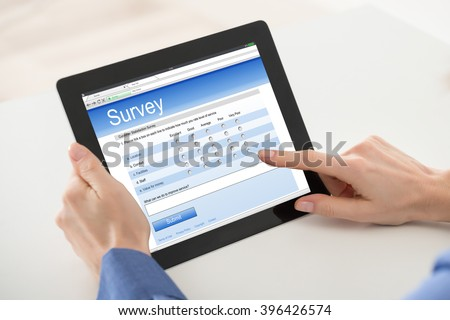 Close-up Of Woman Filling Online Survey Form On Digital Tablet - stock photo