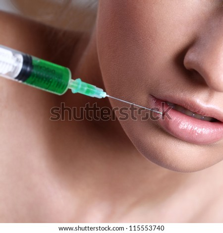 Close up of woman getting an injection in her lips - stock photo