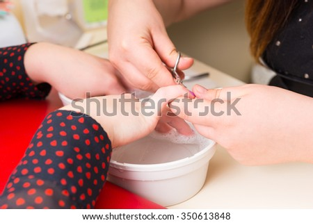 Close Up of Woman Getting Manicure - Esthetician Trimming Cuticles with Small Scissors Over Dish of Soaking Solution in Spa Salon - stock photo