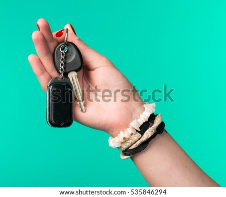 Close-up of  woman hand holding car keys on a green background.Car selling or purchasing concept