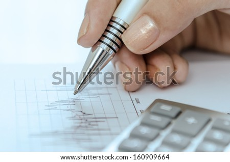 Close up of woman hand holding on graph - stock photo