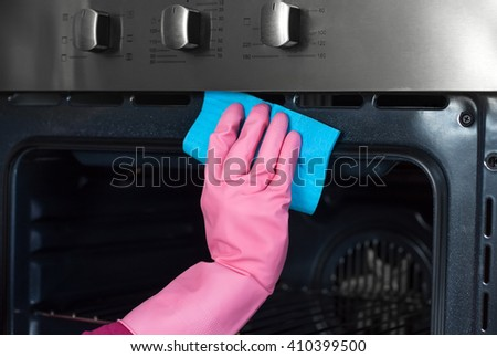 close up of woman hand in protective glove with rag cleaning oven. People housework and housekeeping concept. Cleaning oven - stock photo