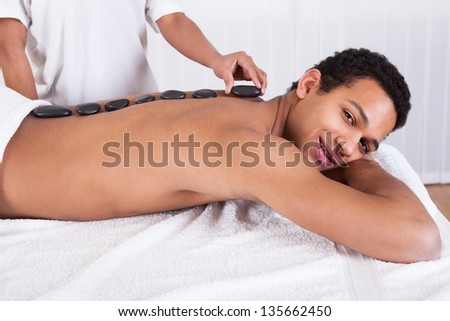 Close-up Of Woman Hand Placing Lastone On Man Back - stock photo