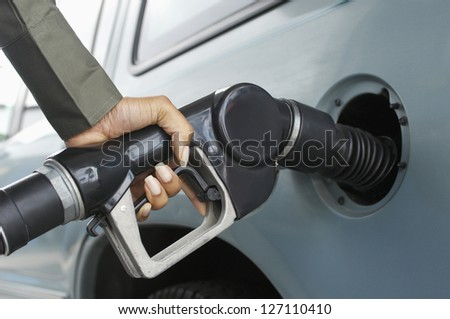Close-up of woman hand refueling car's tank by holding petrol pump nozzle - stock photo