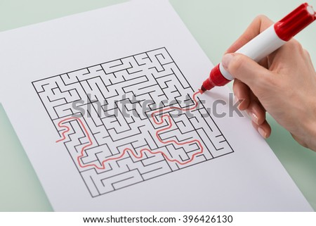 Close-up Of Woman Hand Solving Maze Puzzle With Red Marker